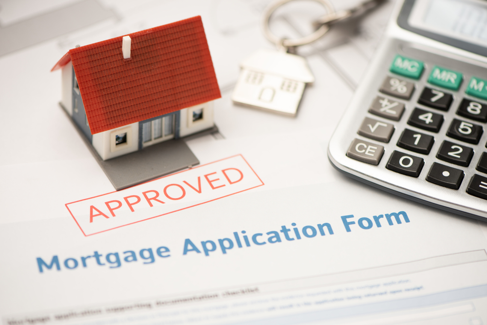 picture of toy house on top of mortgage application form
